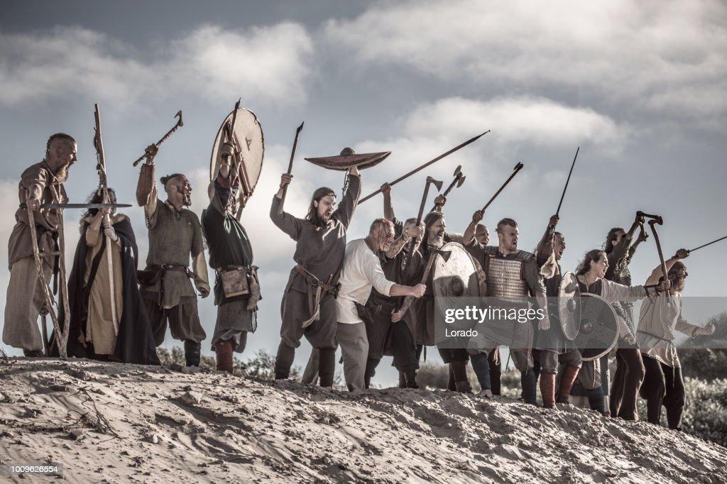 A hoard of Weapon wielding viking warriors on a sandy battlefield dune : Stock Photo