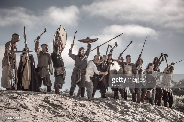a hoard of weapon wielding viking warriors on a sandy battlefield dune - reenactment stock photos and pictures