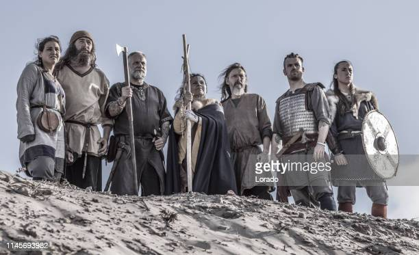 a hoard of weapon wielding viking warriors on a sandy battlefield dune - battlefield stock pictures, royalty-free photos & images