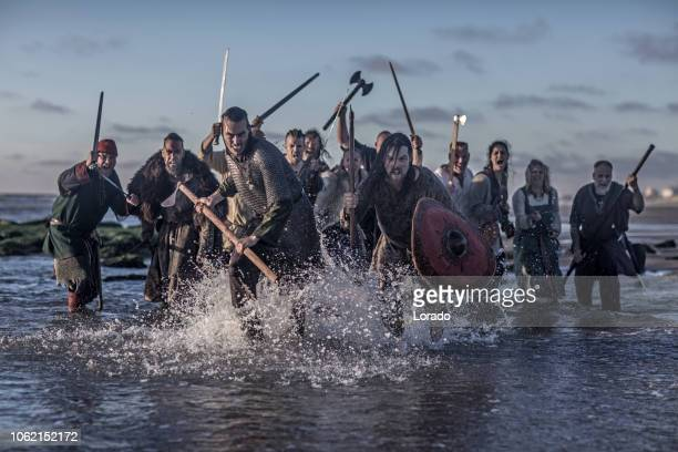 a hoard of weapon wielding viking warriors - barbarian stock photos and pictures