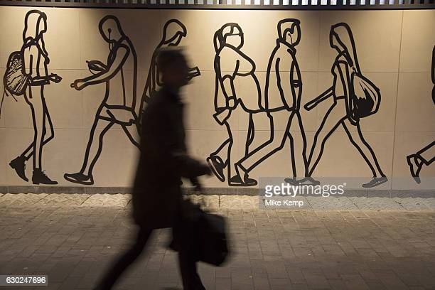 Hoarding depicting people walking by interacts with commuters passing by during rush hour during works at an underground station in London England...
