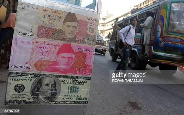 A hoarding display showing currency notes is pictured by the roadside at a local and foreign currency market in Karachi on December 14 2011 AFP PHOTO...