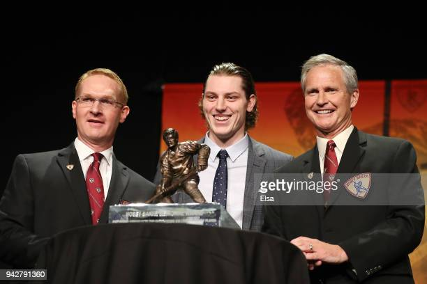 Hobey Baker Chair Peder Melin award winner Adam Gaudette of Northeastern University and the Vancouver Canucks and announcer Tom Hauser pose with the...