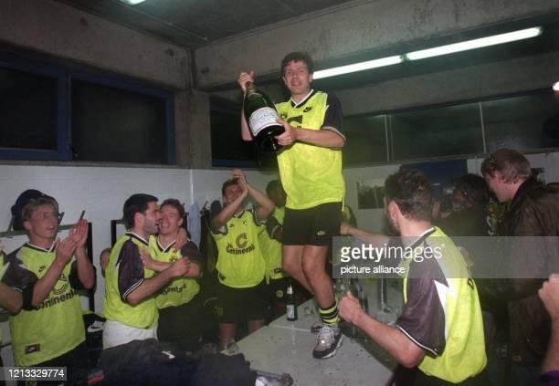 Hoch her geht es am 18.5.1996 in der Kabine von Borussia Dortmund. Während Andreas Möller mit einer Flasche Sekt auf dem Tisch tanzt, klatschen seine...