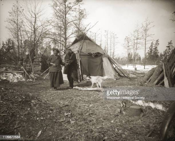 A HoChunk couple and their dog outside of their winter home Black River Falls Wisconsin 1890 A Hudson Bay blanket is hanging over the door opening...