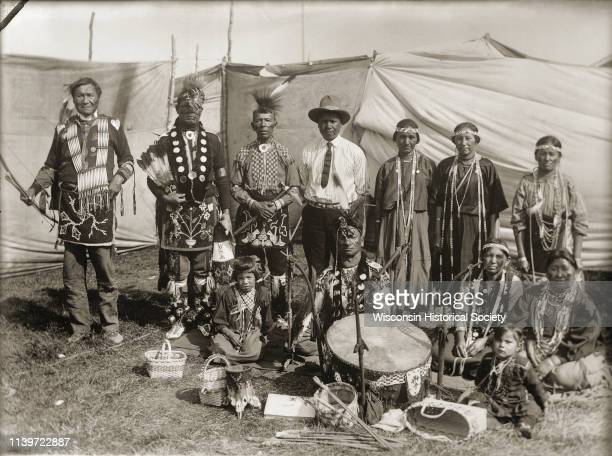HoChunk performers gathered behind a drum and Winnebago baskets at the 1908 Homecoming Black River Falls Wisconsin 1908 Standing from the left are...