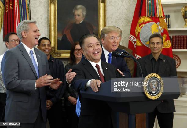 Hock Tan chief executive officer of Broadcom Ltd center speaks as US President Donald Trump center right listens during an announcement in the Oval...