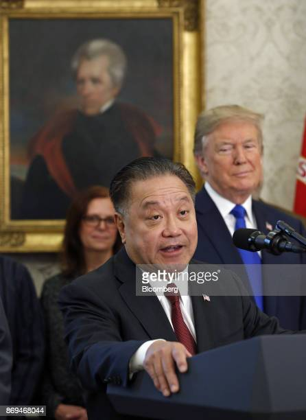 Hock Tan chief executive officer of Broadcom Ltd center speaks while US President Donald Trump listens during an announcement in the Oval Office of...