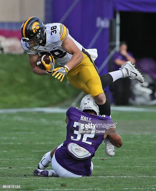 Hockenson of the Iowa Hawkeyes is tackled by Nate Hall of the Northwestern Wildcats at Ryan Field on October 21, 2017 in Evanston, Illinois.