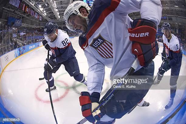 2014 Winter Olympics USA David Backes in action vs Slovakia Tomas Kopecky and Ivan Baranka during Men's Preliminary Round Group A game at Shayba...