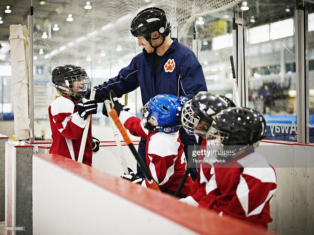 Hockey coach congratulating young female player : Stock Photo
