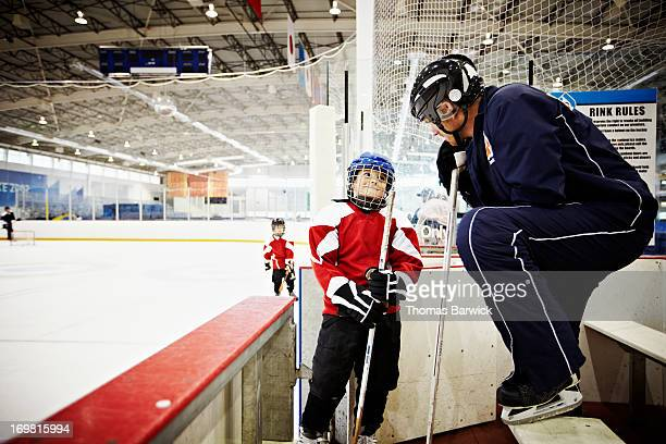 Hockey coach encouraging young hockey player