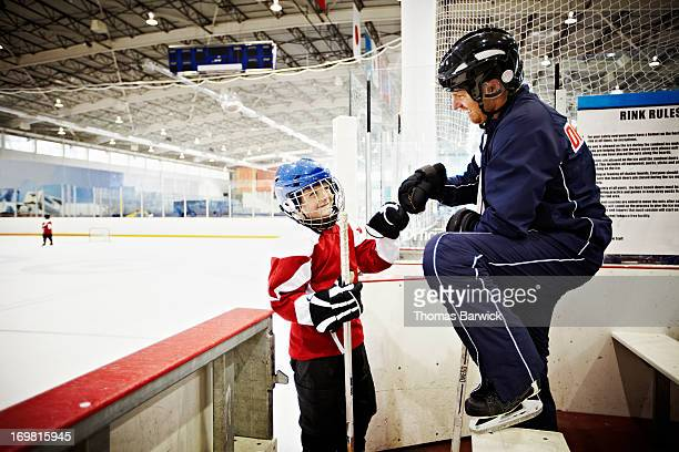 Hockey coach giving young player a fist bump