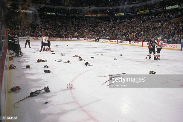 Hockey equipment litters the ice as members of the New York Islanders and the Buffalo Sabres fight Uniondale New York February 1997