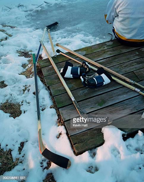 hockey equipment on board, player near by, elevated view - アイスホッケーグローブ ストックフォトと画像