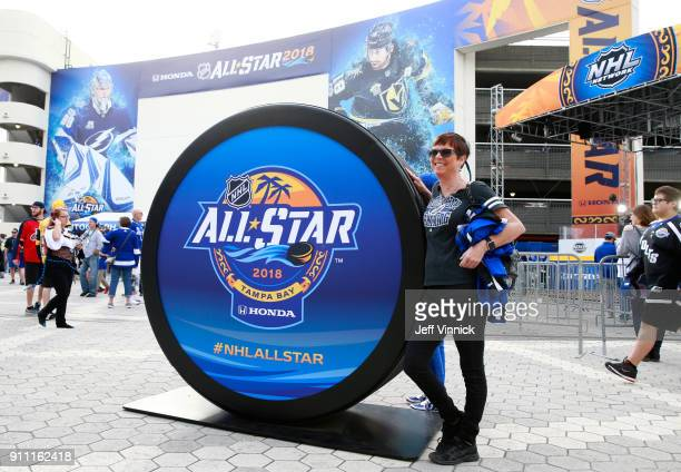 A hockey fan poses next to a large puck prop at the PreGame Mascot Showdown at Amalie Arena on January 27 2018 in Tampa Florida
