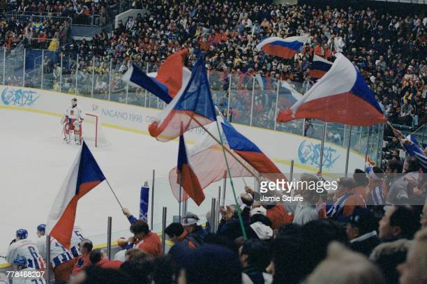 Hockey fans from the Czech Republic wave flags and banners as Dominik Hasek goaltender for the Czech Republic looks on during the Gold Medal game...
