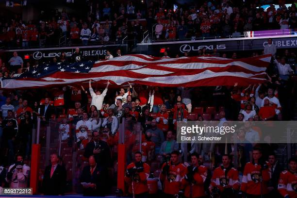 Hockey fans pass the American Flag during opening festivities prior to the start of the game between the Florida Panthers and the Tampa Bay Lightning...