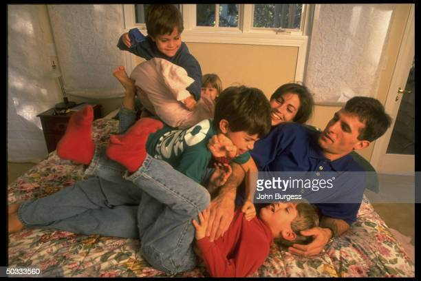 Feature. San Jose Sharks Tony Granato playfully wrestling on bed w. Wife & 4 kids at home.