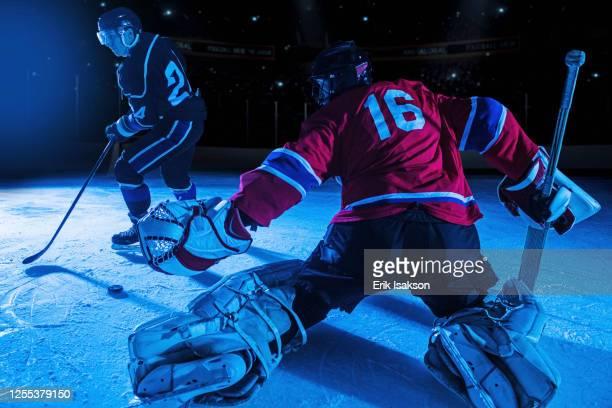 hockey goalie in defensive position against forward - angriffsspieler stock-fotos und bilder