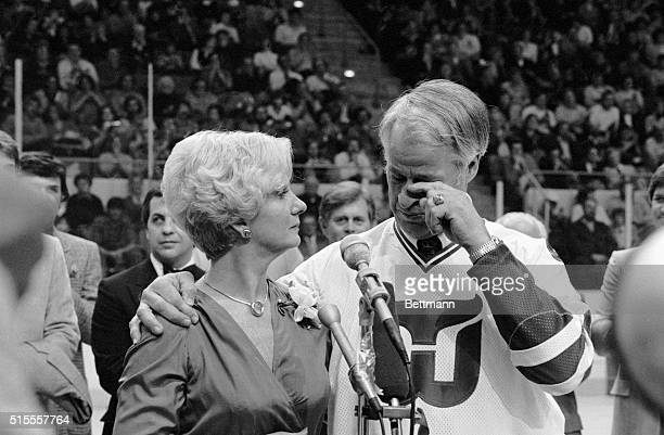 Hockey great Gordie Howe, with his arm around his wife, Colleen, wipes away a tear as he thanks fans during pre-game ceremony in which his jersey,...