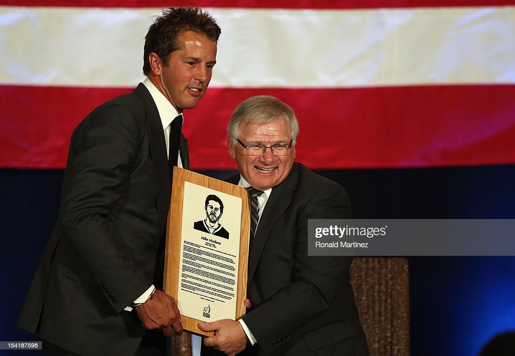 U.S. Hockey Hall of Fame President, Ron DeGregorio presents a plaque to Mike Modano after his induction into the U.S. Hockey Hall of Fame during the 40th annual U.S. Hockey Hall of Fame Induction Ceremony & Dinner at Plaza of the Americas on October 15, 2012 in Dallas, Texas.