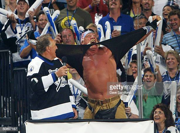 Hockey Hall of Famer Phil Esposito watches as professional wrestler Hulk Hogan rips his shirt off following the singing of the National Anthem by his...
