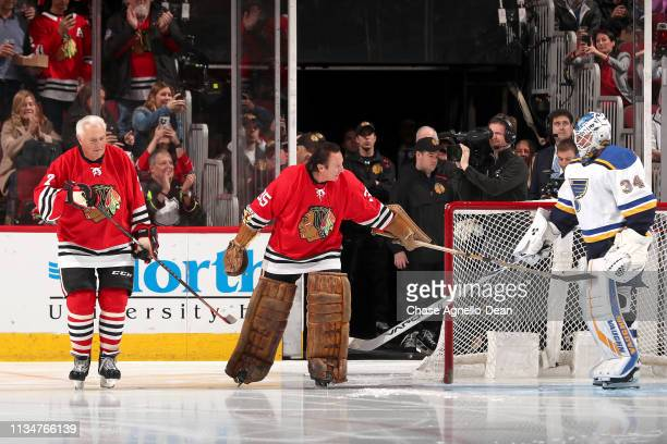 Hockey Hall of Famer Tony Esposito taps goalie Jake Allen of the St Louis Blues as he skates out with his brother Hall of Famer Phil Esposito for the...