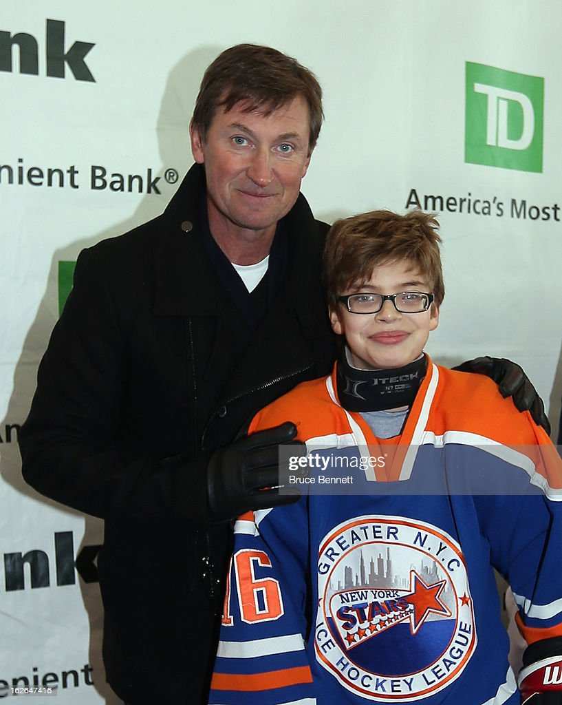 Hockey Hall of Famer Wayne Gretzky poses with youth player Zach Orlowsky at a appearance at the Abe Stark Arena on February 25, 2013 in New York City. The event was organized by TD Bank who donated funds to the Greater New York City Ice Hockey League to replace equipment that was lost or destroyed during Superstorm Sandy.