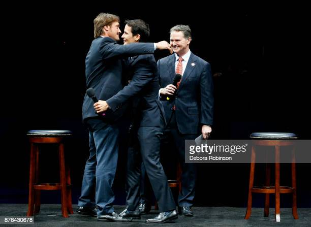 Hockey Hall of Famers and former Anaheim Ducks Teemu Selanne left and Paul Kariya center embrace while Ducks Broadcaster Brian Hayward looks on...