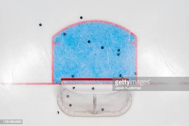 hockey net with pucks from above - eishockey stock-fotos und bilder