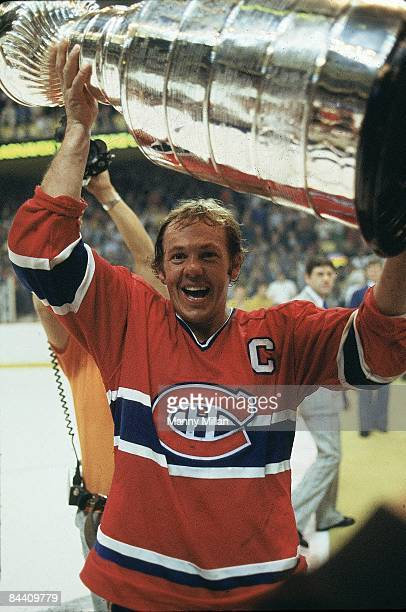 NHL Finals Montreal Canadiens Yvan Cournoyer victorious with Stanley Cup trophy after winning Game 7 and series vs Boston Bruins Boston MA 5/25/1978...