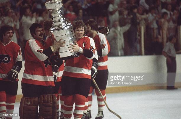 Hockey NHL Finals Philadelphia Flyers goalie Bernie Parent and Bobby Clarke victorious with Stanley Cup trophy after winning game vs Buffalo Sabres...