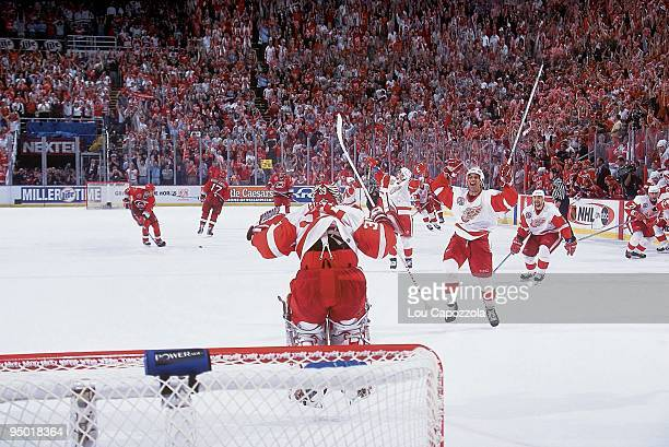 NHL Finals Rear view of Detroit Red Wings goalie Dominik Hasek victorious jumping in air as teammate Chris Chelios skates onto ice with team after...