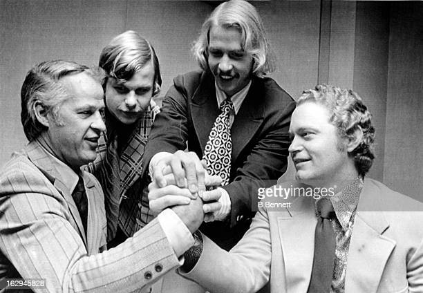 Hockey player Gordie Howe of the Houston Aeros arm wrestles baseball player Rusty Staub of the New York Mets as Marty Howe and Mark Howe help their...
