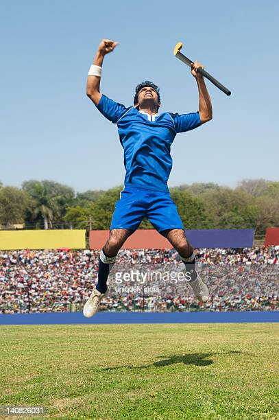 Hockey player jumping in excitement in a field