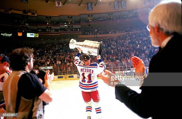 Hockey player Mark Messier of the New York Rangers lifts the Stanley Cup aloft after his team defeated the Vancouver Canucks at Madison Square Garden...