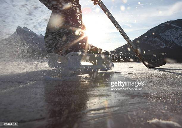 Hockey player turns fast on frozen mountain pond