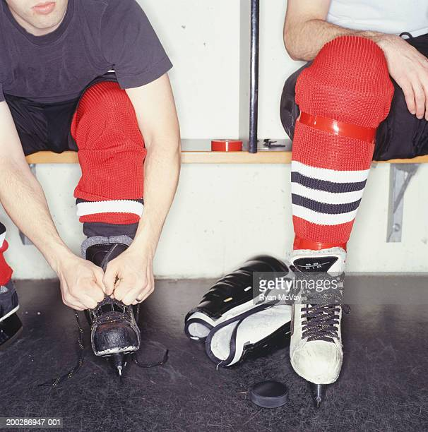hockey players in locker room, low section - hockey skates stock photos and pictures