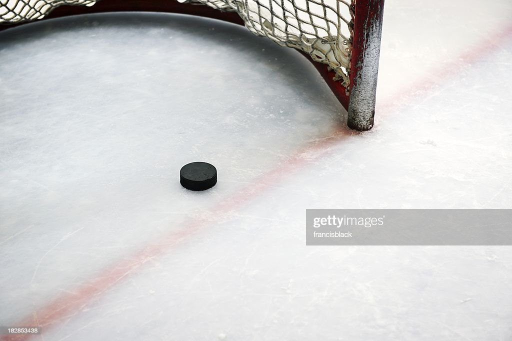 Hockey puck in goal and red line : Stock Photo