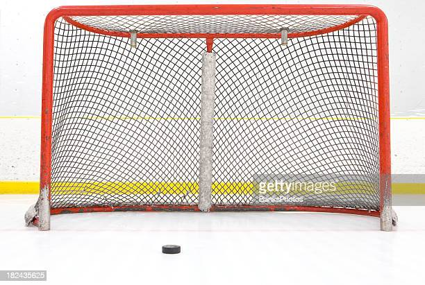 hockey puck near goal net - ice hockey rink stock pictures, royalty-free photos & images