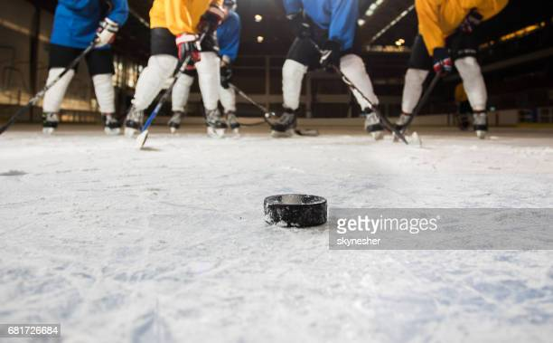 Hockey puck with ice hockey players in the background.