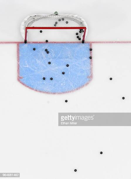Hockey pucks are scattered on the ice around a net during warmups before Game Two of the 2018 NHL Stanley Cup Final at TMobile Arena between the...