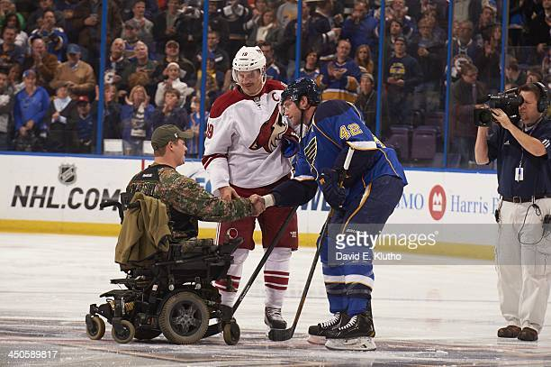 St Louis Blues David Backes and Phoenix Coyotes Shane Doan on ice with corporal Justin McLoud after ceremonial puck drop in honor of Veterans Day...