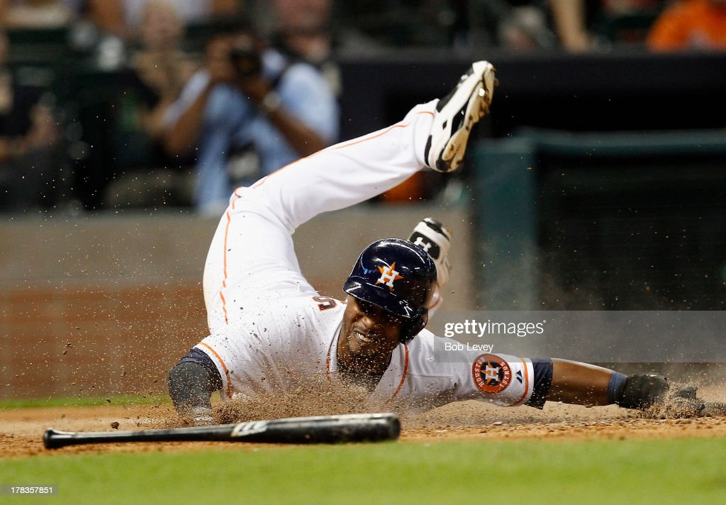L.J. Hoes #28 of the Houston Astros slides to score in the fourth inning on a double by Jason Castro #15 of the Houston Astros against the Seattle Mariners at Minute Maid Park on August 29, 2013 in Houston, Texas.