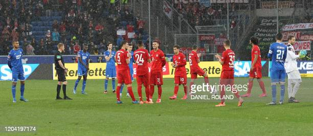Hoffenheim's and Bayern Munich's players wait for the match to be stopped during the German first division Bundesliga football match Hoffenheim v...