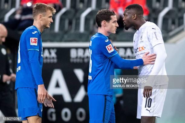 Hoffenheim's Austrian defender Stefan Posch looks on as Hoffenheim's German midfielder Sebastian Rudy holds back Moenchengladbach's French forward...