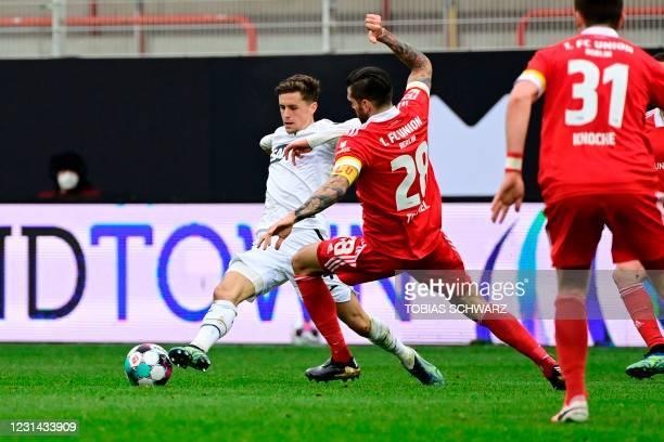 Hoffenheim's Austrian midfielder Christoph Baumgartner and Union Berlin's Austrian defender Christopher Trimmel vie for the ball during the German...