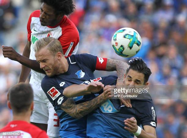 Hoffenheim's German midfielder Kevin Vogt and Hoffenheim's German defender Benjamin Huebner vie for the ball with Augsburg's Brazilian midfielder...