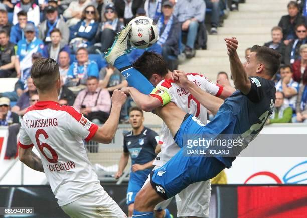 TOPSHOT Hoffenheim's Hungarian forward Adam Szalai vies with Augsburg's Augsburg's Dutch defender Jeffrey Gouweleeuw and Augsburg's Dutch defender...